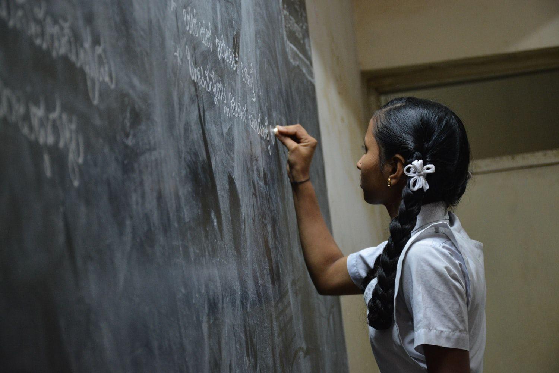 Школьница пишет на доске